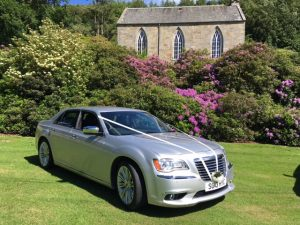 silver wedding car in front of rural church