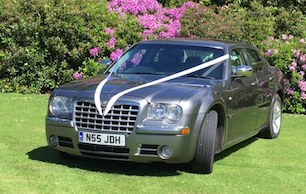 Wedding car with bridal ribbons parked on grass with flowering bush in background