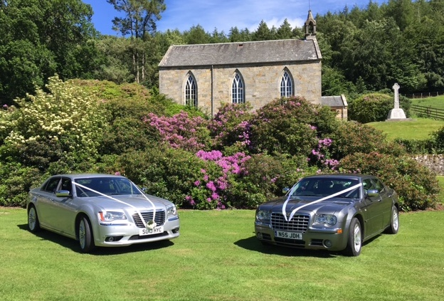 wedding cars on lawn of scenic church garden